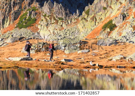 Hikers and mountains reflected by calm waters of glacier lake - stock photo