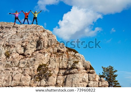 hikers at the top of a rock with their hands up - stock photo