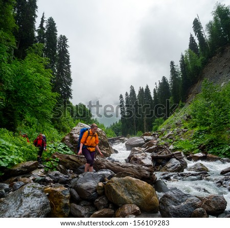 Hikers cross the mountain river ford - stock photo