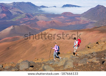 Hikers enjoying walk on amazing mountain trail. Backpacking in Haleakala volcano, incredible view. Couple trekking.  - stock photo