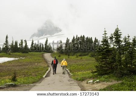 hikers in the snow and fog on Hidden Lake Trail in Glacier National Park - stock photo
