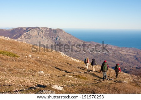 Hikers is walking on plateau in Crimea mountains - stock photo