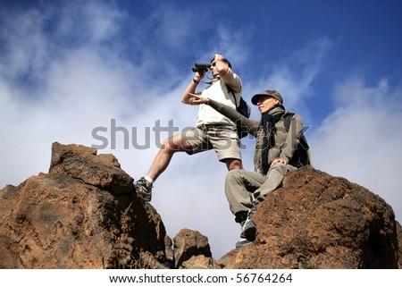 Hikers looking away through binoculars - stock photo
