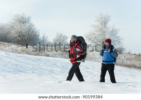 Hikers on the snow on winter field - stock photo