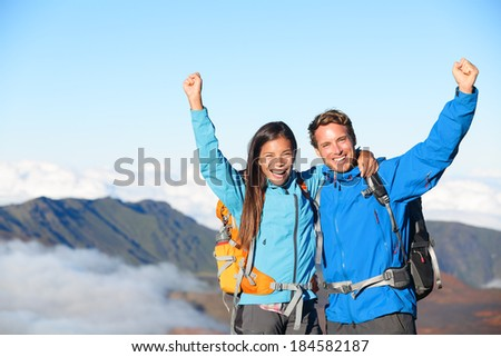 Hikers - people hiking cheering on summit top with view on volcano. Hiker couple looking at beautiful landscape of mountain volcanoes, Haleakala national park Hawaii, USA. People exited and happy. - stock photo