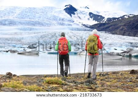 Hikers - people on adventure travel on Iceland. Hiking man man woman walking to glacier and glacial lagoon / lake of Fjallsarlon, Vatna glacier, Vatnajokull National Park. Couple in active lifestyle. - stock photo