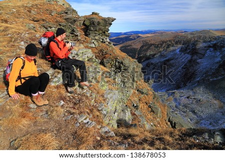 Hikers sitting and admiring the beautiful mountains and valleys - stock photo
