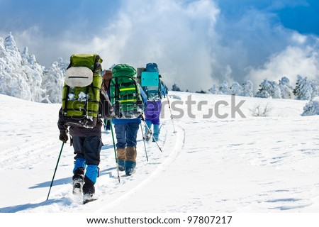 Hikers walk in snow mountain - stock photo