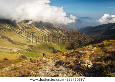 Hikers walking on a steep footpath with great panoramic view and autumnal vivid colors. - stock photo