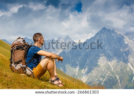 Hikers with backpack sitting on the grass in the mountain and looking into the distance - stock photo