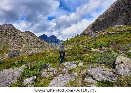 Hiking. A woman with a large backpack in rubber boots walks on a mountain path - stock photo