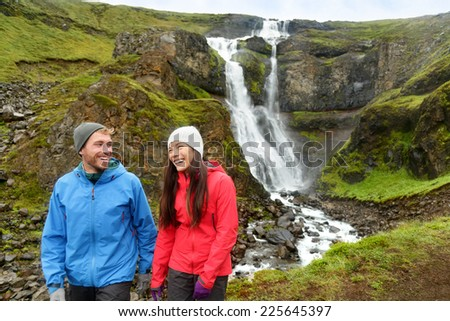 Hiking active couple fun by waterfall in Iceland nature. People walking talking smiling happy in Icelandic tourist landscape in summer. Hiking couple laughing. - stock photo