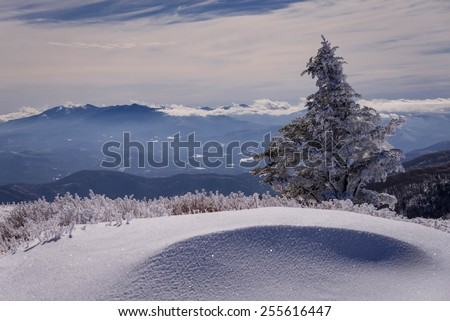 Hiking along the Appalachian Trail with snow drifts on both sides of the trail as we look over the peaks and valleys of the distant mountains from the top of Round Bald at Roan Mountain. - stock photo