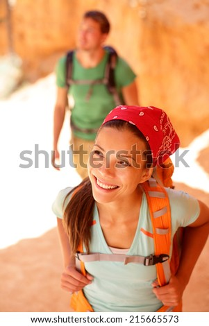 Hiking - Asian woman hiker in Bryce Canyon. Couple walking smiling happy together. Multiracial couple, young Asian woman and Caucasian man in Bryce Canyon National Park landscape, Utah, United States. - stock photo