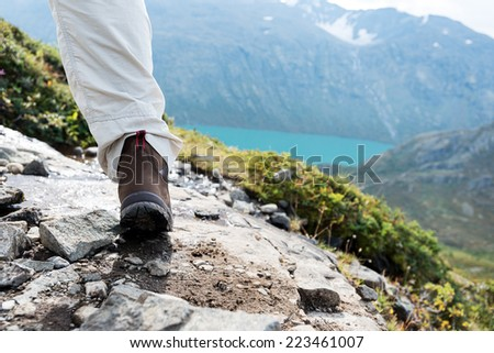 Hiking boot close up on rock in mountains - stock photo