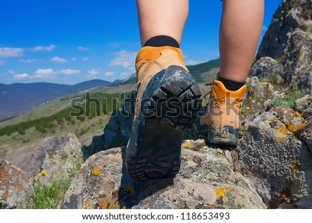 Hiking boot closeup on mountain rocks - stock photo