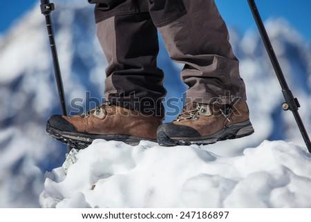 Hiking boot closeup on mountain rocks - stock photo