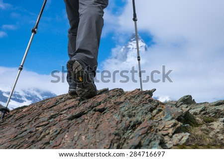 Hiking boots and poles closeup with blurred Matterhorn on background, go to the end. - stock photo