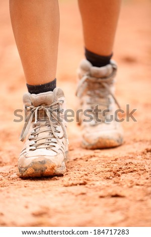 Hiking boots - close up of dirty hiker shoes. Woman feet and female hikers footwear shoe walking on dirt trail hike path outdoor in nature. - stock photo
