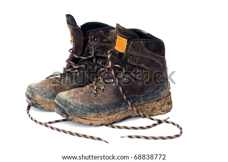 Hiking boots, well worn and muddy, isolated on white. - stock photo