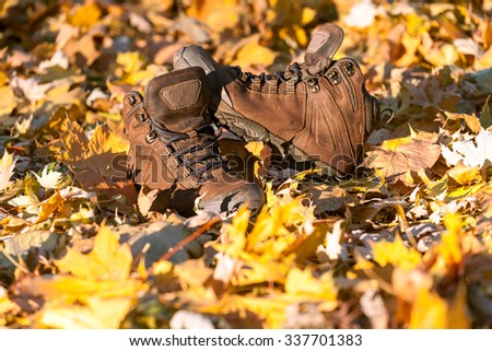 Hiking boots, well worn and muddy on the forest floor - stock photo