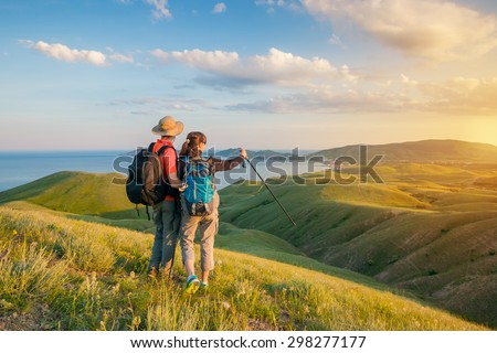 Hiking couple. Hikers with backpacks standing on mountain and enjoying sunrise.  - stock photo