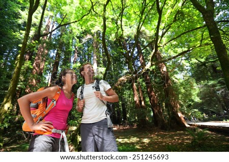 Hiking couple in forest Redwoods, San Francisco. Hiker couple walking among Redwood trees near San Francisco, California, USA. Multiracial couple, young Asian woman and Caucasian man. - stock photo
