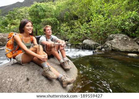 Hiking couple of hikers in outdoor activity wearing backpacks relaxing. Woman and man hiker looking with smiling happy. Healthy lifestyle image from Iao Valley State Park, Wailuku, Maui, Hawaii, USA. - stock photo