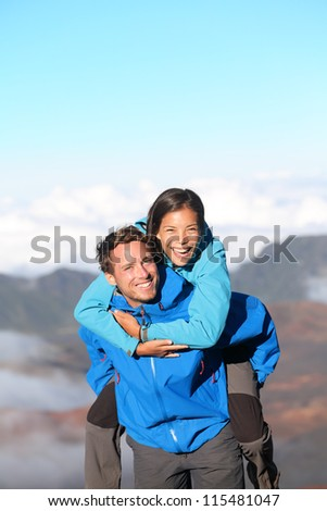 Hiking couple piggybacking happy and cheerful on hike in high mountains. Joyful smiling interracial couple having fun together. Caucasian man hiker and Asian woman hiker. - stock photo