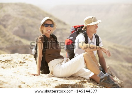 Hiking couple relaxing on top of mountain - stock photo