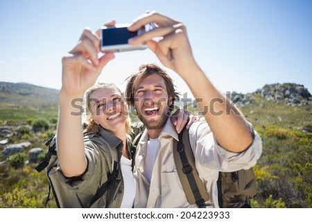 Hiking couple standing on mountain terrain taking a selfie on a sunny day - stock photo