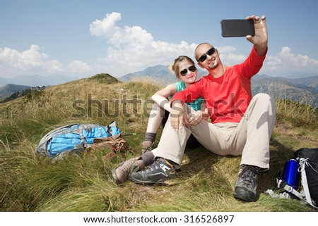 hiking couple taking a self portrait - stock photo