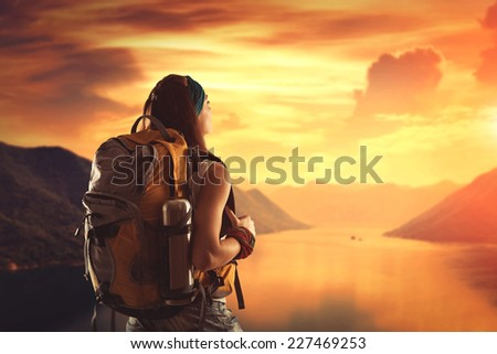 Hiking girl with backpack is looking at sunset - stock photo