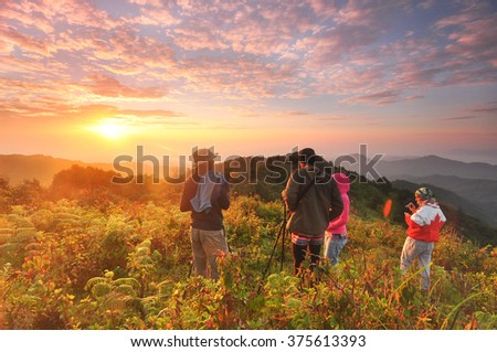 hiking group on top of the mountain and enjoying sunset - stock photo