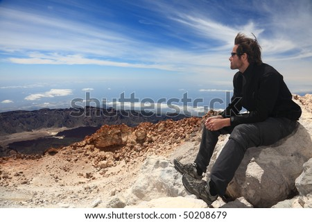 Hiking - Hiker enjoying view. Male hiker sitting and relaxing at the summit of the volcano  Teide on Tenerife. - stock photo