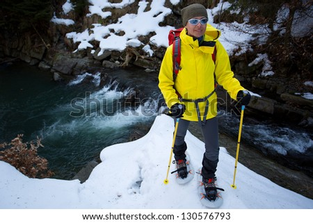 Hiking, hiker in spring mountains, snowshoeing - woman on hike - stock photo