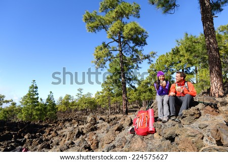 Hiking hikers couple relaxing eating lunch sandwich living healthy active lifestyle in mountain nature. Woman and man hiker sitting during hike on volcano Teide, Tenerife, Canary Islands, Spain. - stock photo