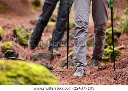 Hiking - Hikers walking in forest with hiking sticks on path trail in mountains. Close up of hiking shoes and boots. Man and woman hiking together. - stock photo