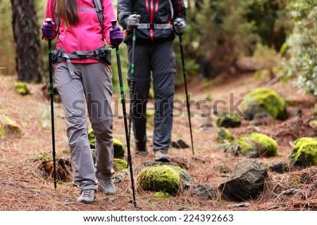 Hiking - Hikers walking in forest with poles on path in mountains. Close up of hiker shoes boots and hiking sticks poles. Man and woman hiking together. - stock photo