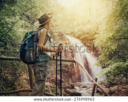 Hiking. Hikers woman with a backpack and a hat looking at a waterfall in the forest. - stock photo