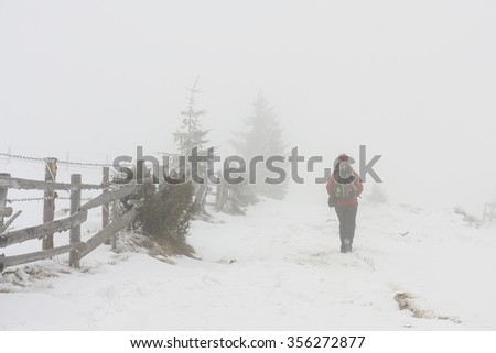 Hiking in bad weather in the winter with a lot of fog - stock photo