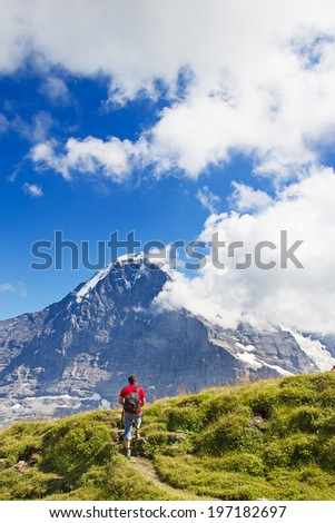 Hiking in the swiss alps: man relaxing after reaching summit. - stock photo