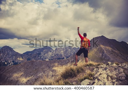 Hiking man, climber or trail runner in mountains, inspirational landscape. Success and business concept.Motivated hiker with backpack looking at beautiful view. Travel, fitness and healthy lifestyle. - stock photo