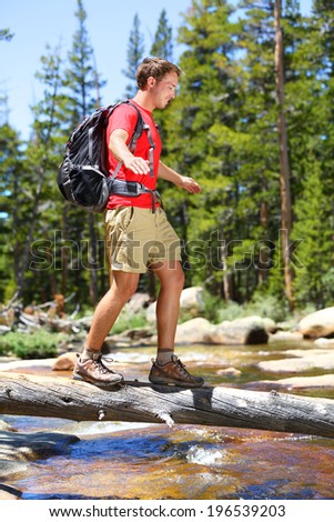 Hiking man crossing river in walking in balance on fallen tree trunk in Yosemite landscape nature forest. Happy male hiker trekking outdoors in Yosemite National Park., California, United States. - stock photo