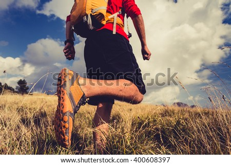 Hiking man or trail runner walking in mountain inspirational landscape. Fitness lifestyle hiker trekker walk in grass, fall autumn nature. Travel in Italy, Europe. Selective focus on a sports shoe.  - stock photo