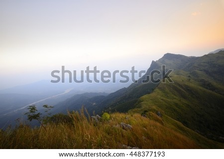 hiking mountain trail. Misty hill road in high mountains. High mountain trail is being covered with fog. Cloudy sky with mountain road view in sunset. - stock photo