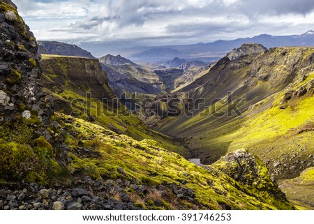 Hiking on Fimmvorduhals, looking through a valley with moss covered mountain sides, Thorsmork visible in the distant. - stock photo