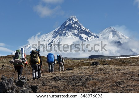Hiking on Kamchatka Peninsula: travelers go to mountains in the background volcanoes: Kamen Volcano, active Klyuchevskoy Volcano, active Bezymianny Volcano on a sunny day. Russian Far East, Kamchatka. - stock photo