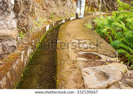 Hiking on the island Madeira along the irrigation channel (Levada) - stock photo