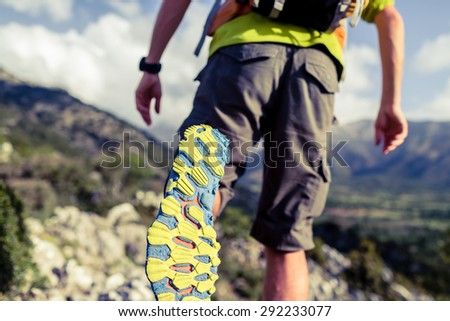 Hiking or running man in beautiful mountains inspirational landscape. Sole of sports shoe and legs of person on rocky footpath. Hiker trekking with backpack.Healthy fitness lifestyle outdoors concept. - stock photo